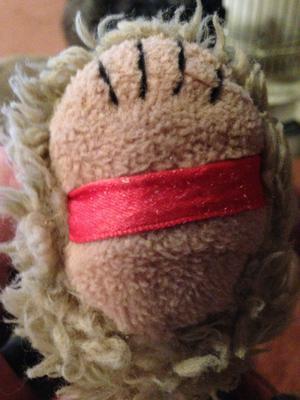 red ribbon on teddy bear foot